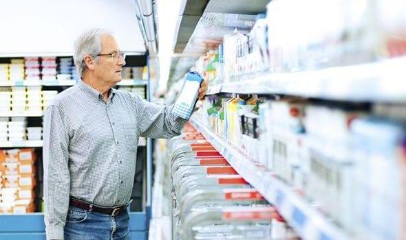 shopper choosing carton of milk