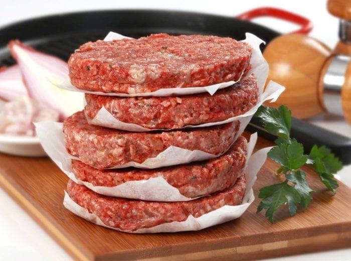 seasoned burgers stacked up