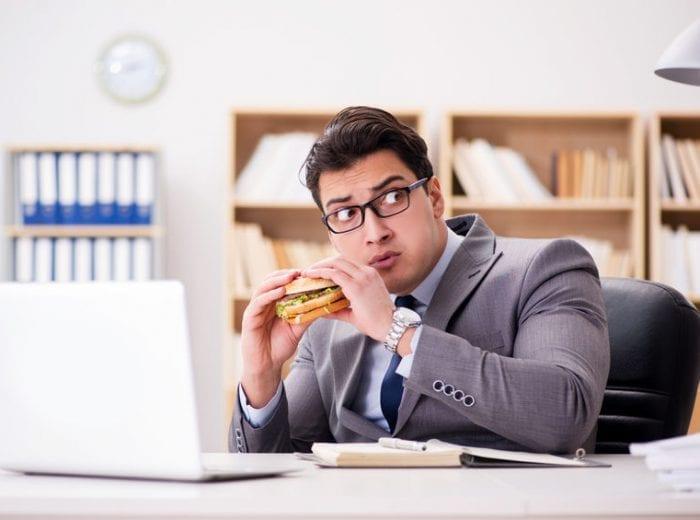 worker eating hot meal at desk