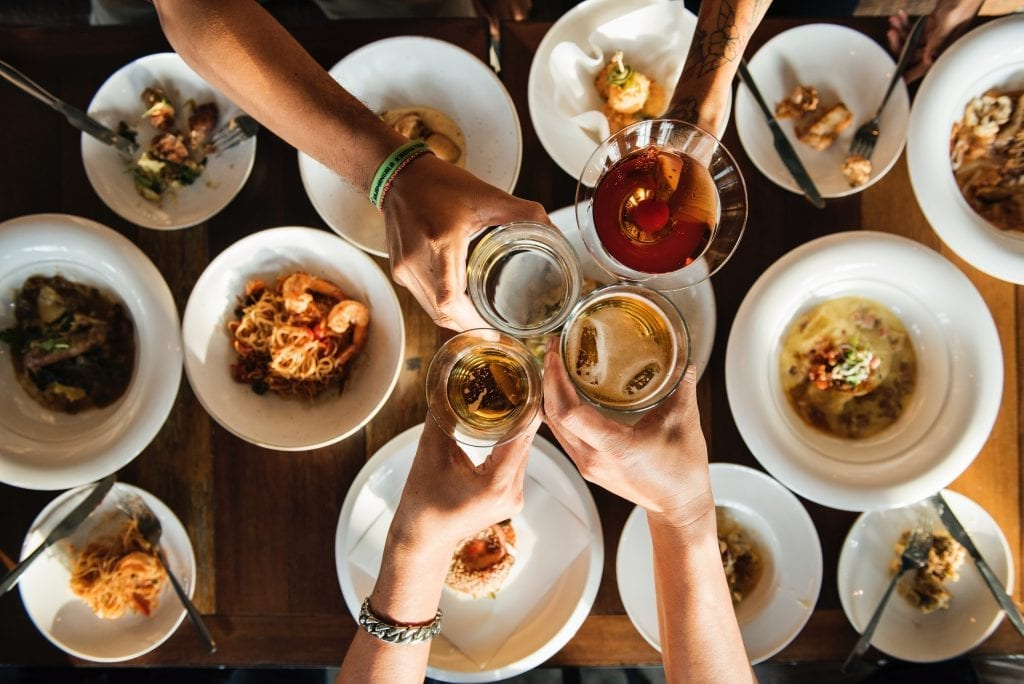 cheers with glasses over table of food