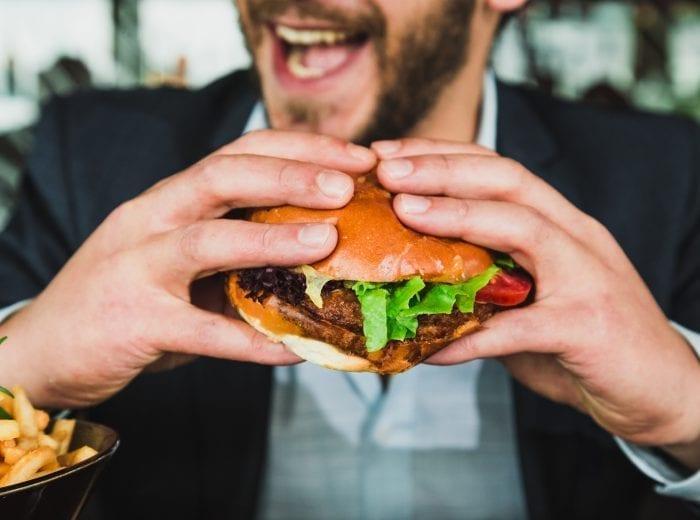 man holding large burger