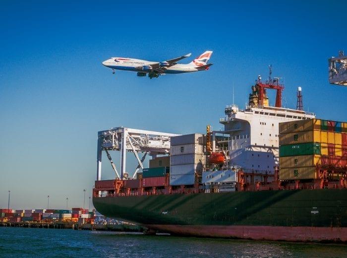 aeroplane flying over cargo ship